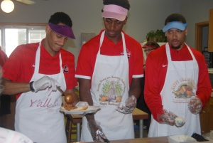 Players serve food at Curt's Kitchen