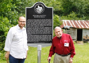 Photo of the historical marker. Caleb Moore and John Britt stand on either side.